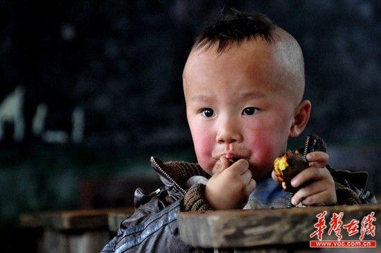 """新晃县洞坪乡大坪坡村彭仪吃着红薯,这是他最""""丰盛""""的午餐,吃的津津有味。(记者:王立三摄)"""
