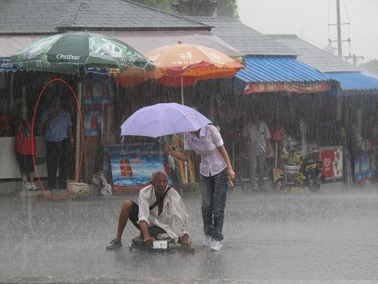 粉衣女孩为残疾老人撑伞,图中制服男正在一旁观望。图片来源:中国江苏网