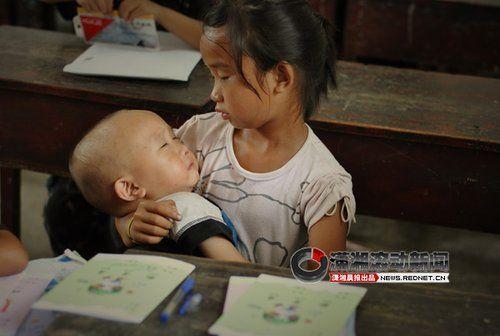 (弟弟哭闹了,姐姐赶忙抱在怀里哄他睡觉。图/潇湘晨报摄友团 卢七星)