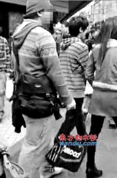 偷拍相机就藏在购物袋(图中圈出)中,男子将袋口对准女性裙底偷拍。视频截图