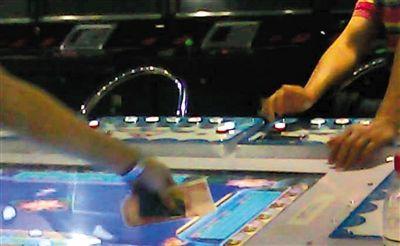 7月4日,服务员正拿起玩家丢来的会员卡和一叠现金,准备去吧台买分充值。
