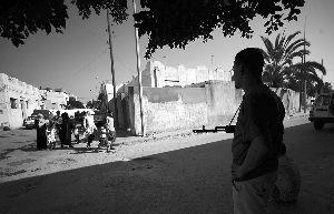 22日,的黎波里,一名反对派武装人员注视着走过的民众。