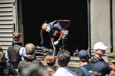 乌克兰托列兹,欧安组织代表登上装载遇难者遗体的冷藏车进行检查。