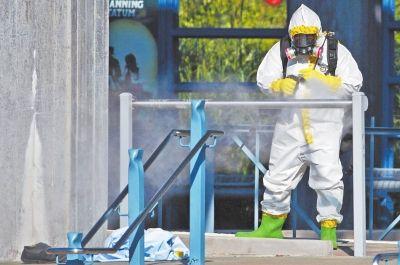 10月18日,在美国达拉斯的一个车站,一名身着隔离服的工作人员正在喷洒消毒药水。当日,一名女性在达拉斯的一个车站病倒,病情症状疑似感染埃博拉病毒。新华社发