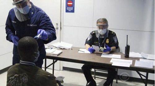 美国机场工作人员对乘客进行体温检查(资料图)