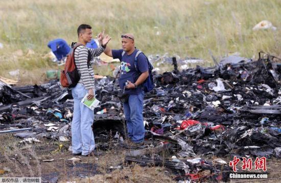 资料图:当地时间2014年7月22日,乌克兰顿涅茨克地区,民间武装、欧安组织成员以及一支马来西亚空难调查团在坠机现场勘查。