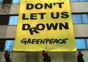 2000 年,COP6 会议在荷兰海牙召开,但这次会议无疾而终,图为NGO组织在张贴抗议的横幅