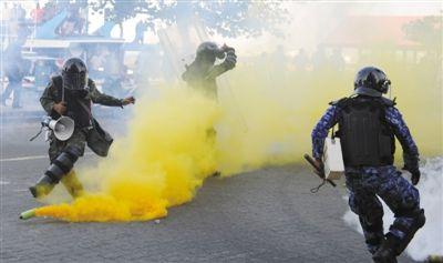 8日,马累,警察在催泪弹的烟雾中穿行。