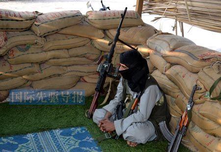 """也门国内种种乱象,是恐怖主义生根发芽的主要原因。图为3月31日,一名疑似""""基地""""组织的武装份子坐在也门南部省份的一处据点内。法新社"""
