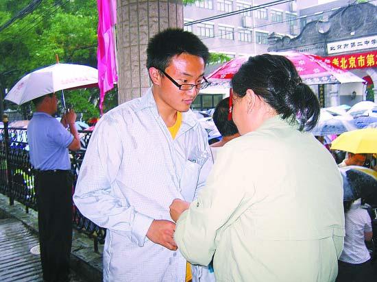 北京2中考点外,妈妈为刚出考场的儿子添加衣服。实习生 郭 莉摄