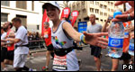 A marathon runner taking a drink