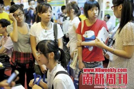 7月4日,一群学生在广州出国留学展上咨询校方代表。