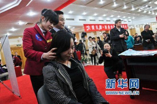3月17日,大学生严丹在拍卖会上展示服务技艺。