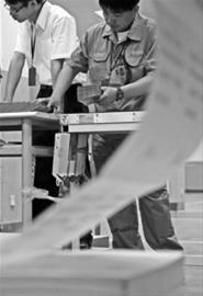 昨晚,邮政广告商函局内,一台台打印高考成绩单的机器飞快运作着。为了避免失误,这些成绩单还将经过人工审查。 晨报记者 吴磊 实习生 肖允 现场图片