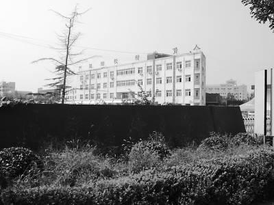 """""""北软科技学院""""南校区校门口,深红色的大理石底座上还依稀能看到""""北京自修大学""""的字迹。"""