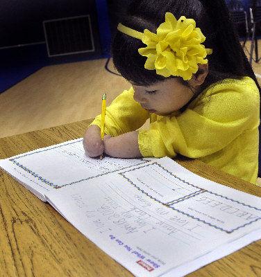 双臂手肘以下残缺的宾州匹兹堡七岁女孩Annie Clark,获得Zaner-Bloser出版社举办的全国写字大赛冠军。(美国《世界日报》援引美联社)