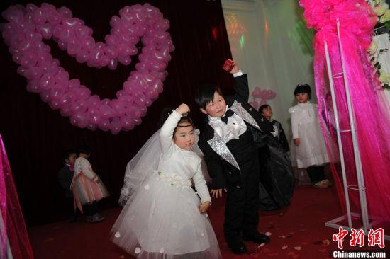 """1月11日,河南郑州一家幼儿园为100多名""""自由恋爱""""的孩子举办了一场""""集体婚礼""""。小""""新郎""""和小""""新娘""""的家长们也在婚礼现场见证。张翼飞 摄 图片来源:CFP视觉中国 3"""