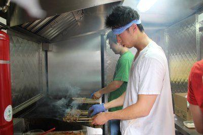 """""""无二烧烤""""餐车共同创办人刘晓正在餐车内忙碌,烧烤车内的高温工作人员饱受辛苦。(美国《世界日报》/刘晨懿之 摄)"""