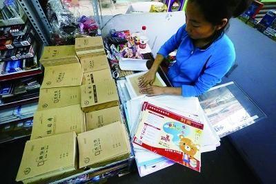 文具店工作人员正在帮家长包本皮 摄/法制晚报记者 曹博远