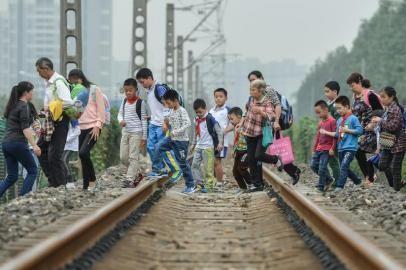 每逢学校放学时,便出现浩浩荡荡的穿越铁路的大军。郝飞摄