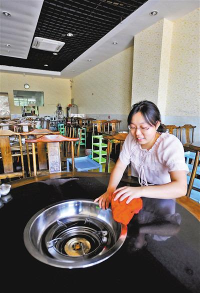 昨日,南岸弹子石,李密在自己的火锅店内收拾餐桌。