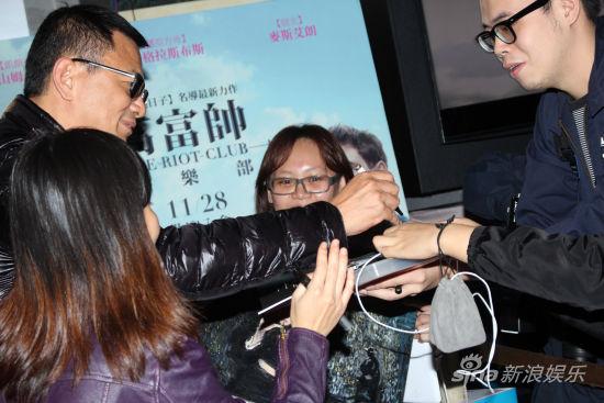 王家卫(左)帮影迷签名