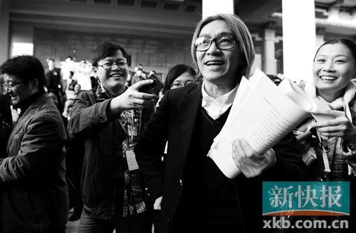 昨天,省政协十一届二次会议开幕,周星驰委员拿着厚厚的一叠材料面对记者。 新快报记者 夏世焱/摄