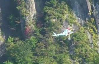 图文:警方搜索臼井仪人-直升飞机飞行在峻岭中
