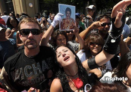 """當地時間七月七日上午,邁克爾·傑克遜的公衆悼念活動在洛杉磯斯坦普斯體育中心舉行。數百名沒有入場券的歌迷聚集在附近的警戒綫外高呼邁克爾的名字,共同悼念一代""""流行天王""""。中新社發張煒 攝"""