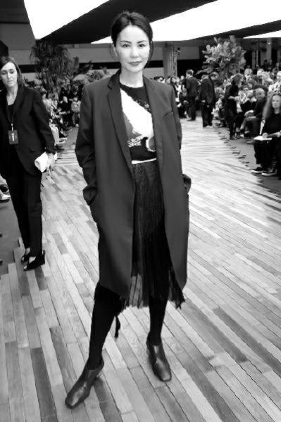 2014秋冬巴黎时装周,王菲穿着低调观秀,蓝色长西装套装搭配印花T恤和纱裙,气场依旧