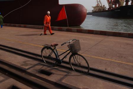 码头工人带缆系泊。