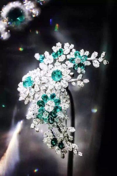 镶嵌在弹簧上的钻石,与祖母绿宝石相映成辉。轻移玉步时,花枝随之颤动,流光溢金。
