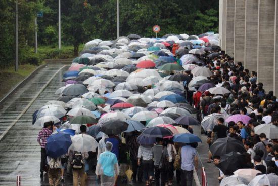 一般日次日因天雨而撑伞等候入场的参观民众