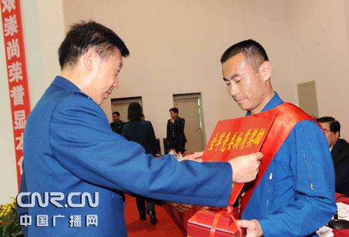空军副司令员杨东明中将为成功处置空中重大特情的特级飞行员李峰颁发一等功证书和空军功勋飞行员金质奖章