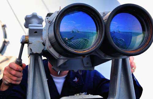 """7月2日,美国海军最新型两栖船坞登陆舰LPD-18新奥尔良号在南海海域进行海上燃油货物补给。一名美军水手长正从导弹巡洋舰""""尚普兰湖""""号上观察新奥尔良号"""
