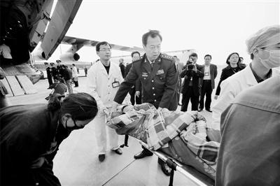 成都军区空军副参谋长战永胜在空运现场指挥转运伤员。一位母亲向自己孩子的救助者深鞠一躬。本报特约记者刘应华摄