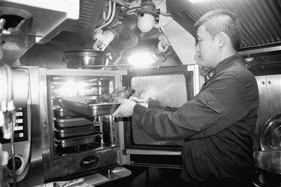 炊事员通过蒸箱加热集成食品。谭依娜摄