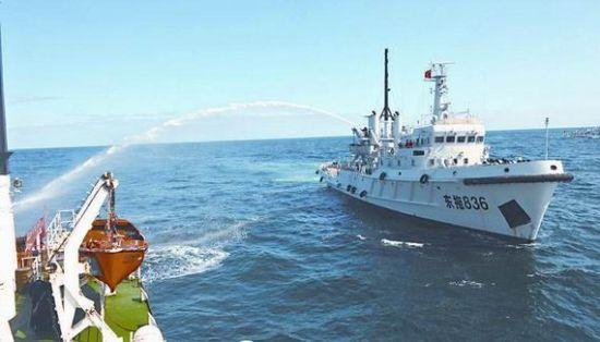 海军拖船利用消防炮向受损渔政船喷射水柱灭火。