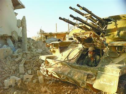 在叙利亚西南部的古赛尔镇,一名叙利亚士兵从坦克内向外看。