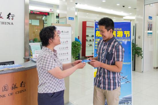 """7月18日上午,在中国银行克拉玛依市石油分行营业部,13岁的卯域诚从行长倪素芬手里接取了""""2013中国新疆•克拉玛依航空节""""的第一张票。"""