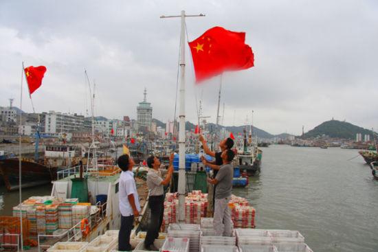 资料图:五星红旗在渔船上升起。