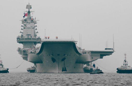 """资料图:中国首艘航母""""辽宁舰""""返回了大连港。""""辽宁舰""""上一次进入大连造船厂船坞是在2012年1月,据分析""""辽宁舰""""试航至今已近两年半,有可能返回造船厂进行中期维护保养。图为网友拍到的返回大连港口的辽宁舰航母"""