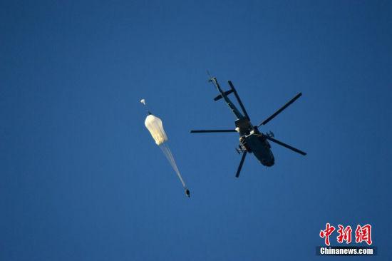 """本地时刻3日,2015国际军事竞赛""""空降排""""野战技术比赛在梁赞举办。图为在竞赛中,参赛甲士从直升飞机上跳伞。"""