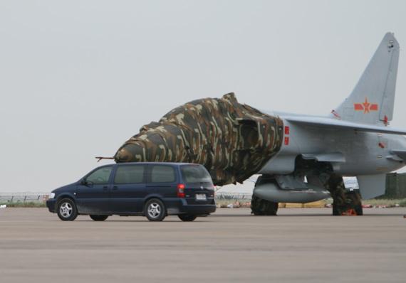 军方专车从飞豹战机旁边驶过