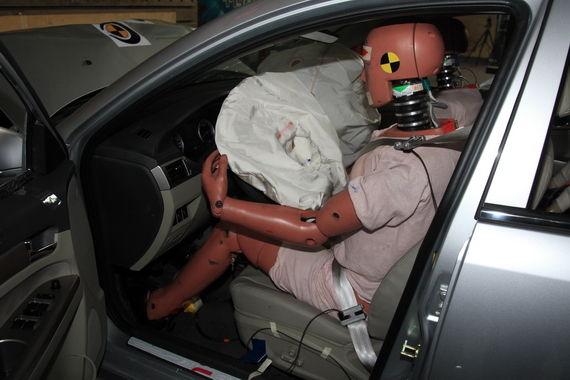 安全气囊弹出,假人坐姿保持良好,内饰部件五边形