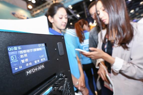 在2015全球移动互联网大会福特展台上,观众体验智能手机应用程序与福特AppLink平台相连接