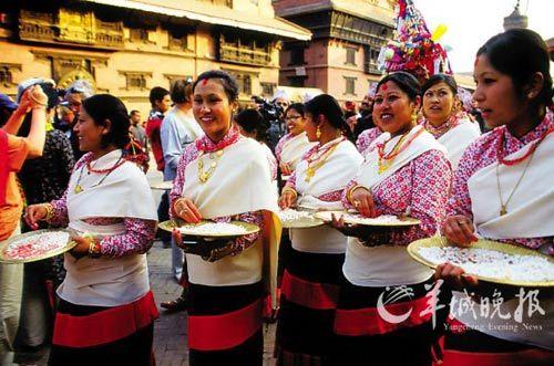 盛装的妇女节日期间在大街上向路人派吉祥