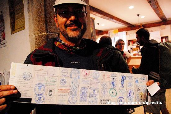 全程徒步的朝圣者手捧盖满纪念章的证书 七色地图/摄 新浪旅游配图