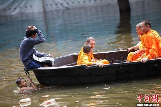 当地时间10月29日,泰国首都曼谷洪水威胁警报仍未解除,一些被困市民尚需转移。图为当天下午有市民将被困洪患区的僧侣往安全的地方转移。中新社发 余显伦 摄