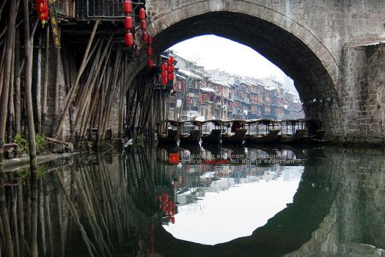 新浪旅游配图:透过桥洞看吊脚楼 摄影:泡鱼儿